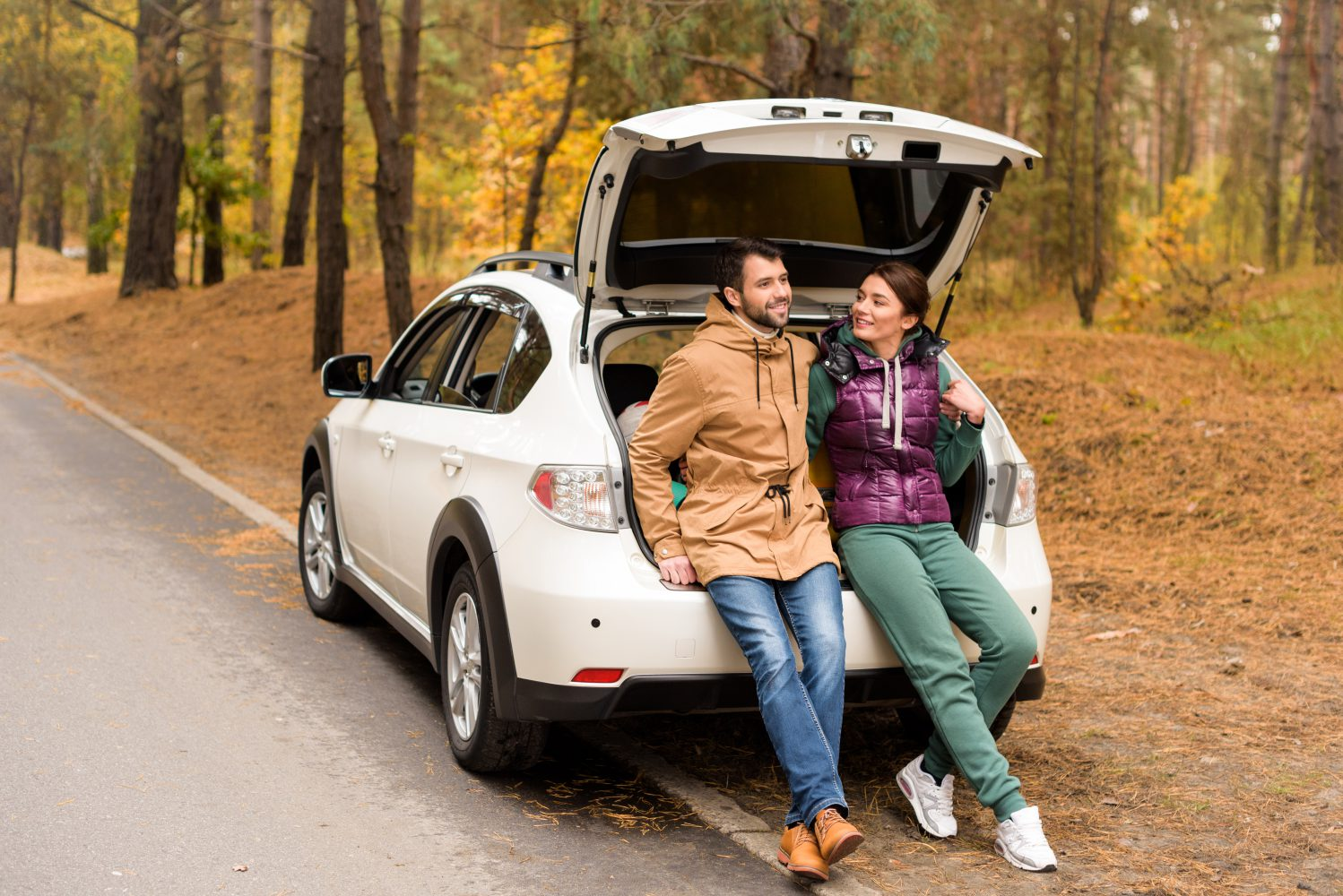 Young couple sitting on car